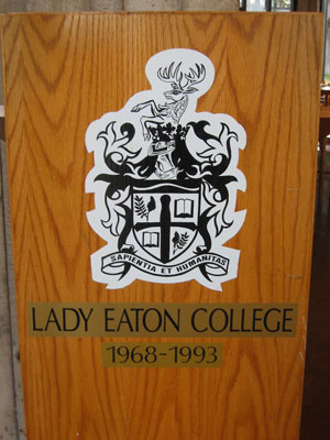 [A dining hall podium with the coat of arms of Lady Eaton College]
